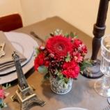 『赤いお花のアレンジメントでテーブルコーディネート』の画像