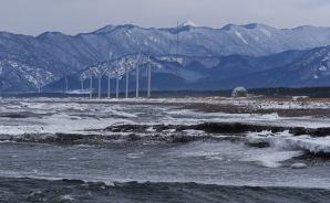 「荒れる日本海と白神の山並み」