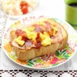 『焼いた食パンの上にスクランブルエッグとカリカリベーコンとケチャップをかけた朝食』の画像